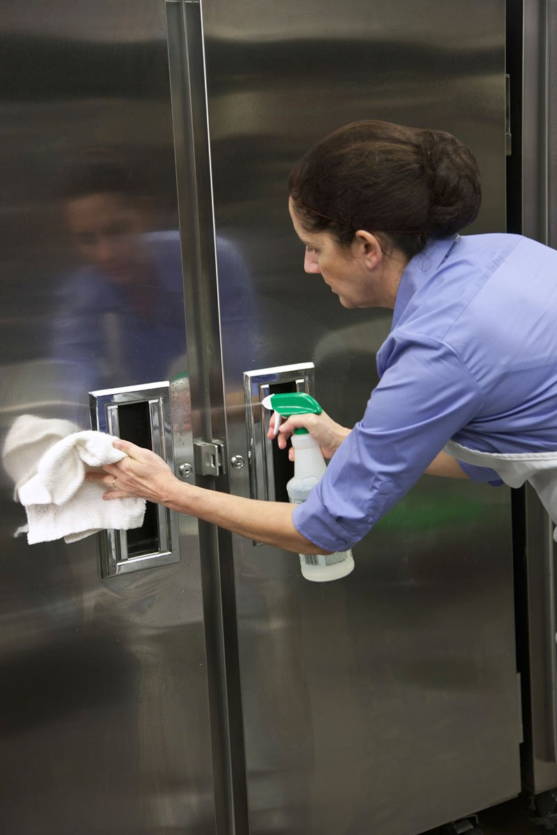 Woman cleaning and sanitizing refrigerator door